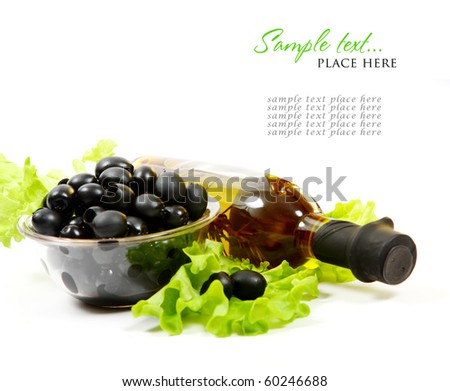 A bottle of olive oil with herbs and black olives isolated on a white background. - stock photo