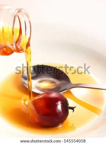 A bottle of palm cooking oil pouring in a white plate - stock photo