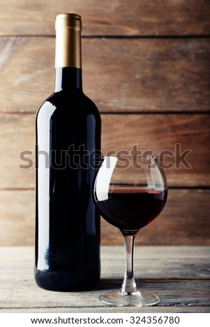 A bottle of red wine and a glass on wooden table