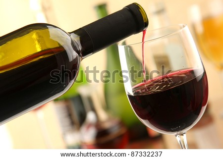 A bottle of red wine and  glasse