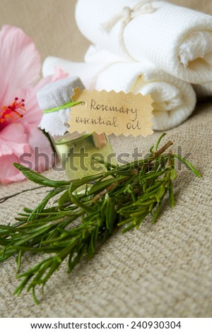 A bottle of rosemary essential oil on a sackcloth. Rosemary twigs and hibiscus flowers in the background - stock photo