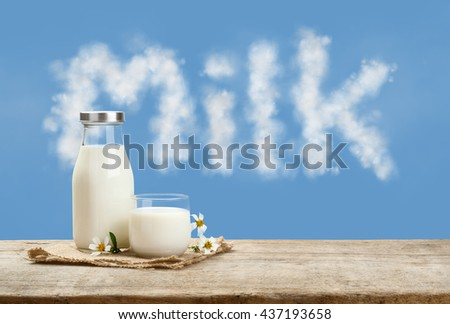 A bottle of rustic milk and glass of milk on a wooden table on a blue sky background, tasty, nutritious and healthy dairy products - stock photo