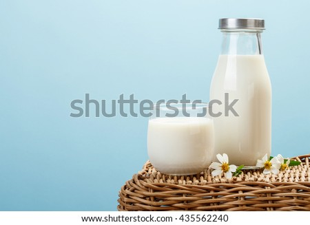 A bottle of rustic milk and glass of milk on wicker on a blue background, tasty, nutritious and healthy dairy products - stock photo