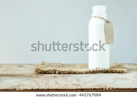 A bottle of rustic milk with empty tag on a wood table on white background, tasty, nutritious and healthy dairy products - stock photo