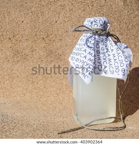 A bottle of shampoo or other means, decorated paper and wrapped a rope, in a retro style, on a cork background. - stock photo