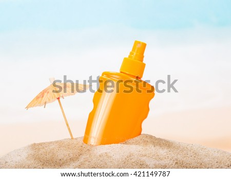 A bottle of sunscreen in the sand against the sea.