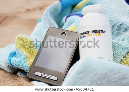 A bottle of sunscreen on a beach towel with mobile phone. Sandy background.