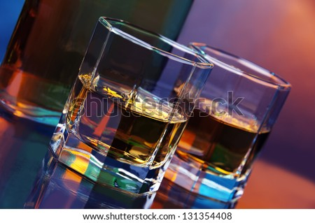a bottle of whiskey and two glasses of whiskey against color background - stock photo