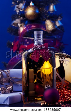 a bottle of whiskey Christmas decoration and Christmas tree at the background