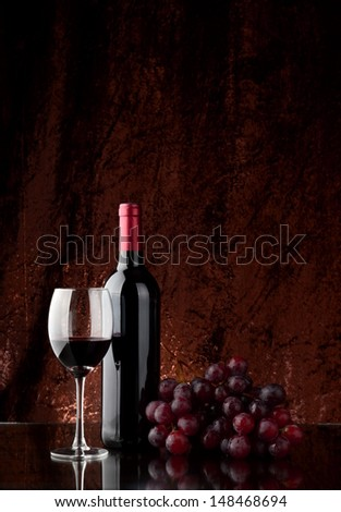 A bottle of wine, a glass and a bunch of grapes