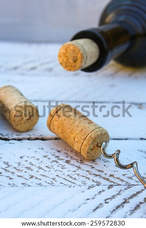 A bottle of wine and a corkscrew in the cork on wooden background - stock photo