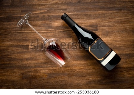 a bottle of wine and wine glass on old wood background. Food background. - stock photo