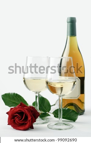A bottle of wine, two wine glasses and a rose, all on white background - stock photo