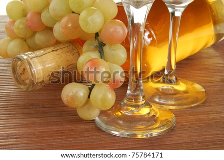 A bottle of wine with a bunch of grapes