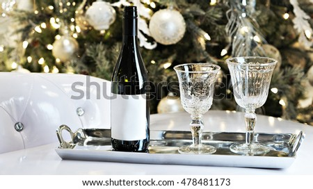 a bottle of wine with vintage glasses and a blurry Christmas tree in background