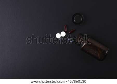 A bottle, pills and herb capsules on black background with copyspace area. - stock photo