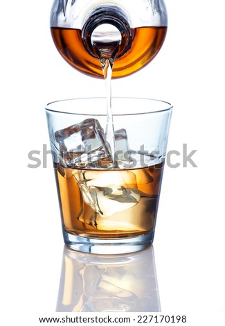 A bottle pouring a drink. Drink could be whiskey, dark rum, bourbon, brandy or any other similar colored alcohol. - stock photo