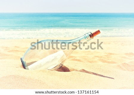 A bottle with a letter of distress in the sand on the beach. In the summer and warm colors. - stock photo