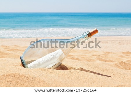 A bottle with a letter of distress on the beach. Summer. - stock photo