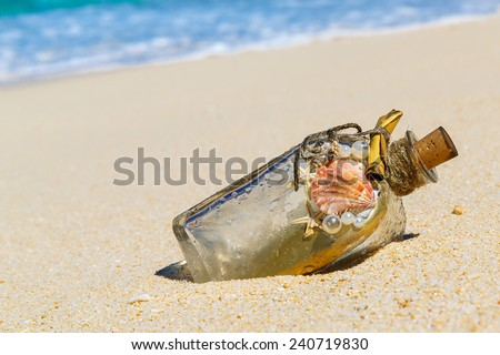 A bottle with a message, which made the sea on the sand of a tropical desert island. Design accessories. - stock photo