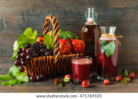 A bottles of fresh grape and apple juice on rustic decor with fresh autumn fruits