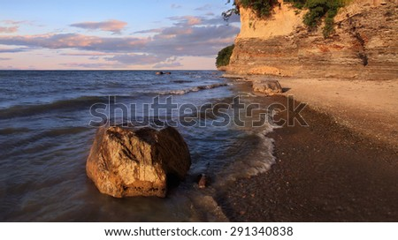 A Boulder Sitting In The Surf With Cliffs Behind Radiating Morning Light, Lake Erie At Barcelona Beach, New York, USA - stock photo