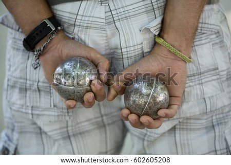 A boules player with one metal ball in each hand, held behind his back