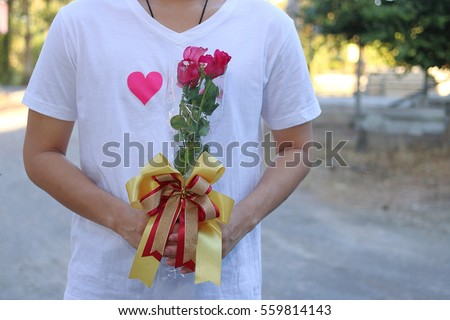 A Bouquet of beautiful red roses is held by young handsome man in white shirt. Valentine's day or dating concept