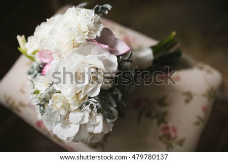 a bouquet of carnations and other white flowers lying on the couch