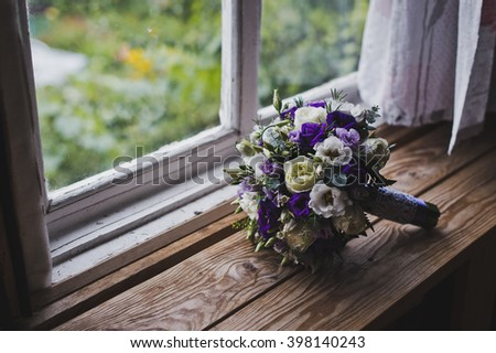 A bouquet of flowers lying on a wooden window sill.