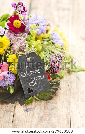 "a bouquet of flowers with a tag saying: ""Love you"""