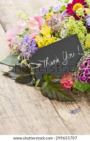 "a bouquet of flowers with a tag saying: ""Thank you"""