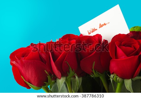 A bouquet of red roses against sky blue background.  A white message card shows 'With Love' in red handwriting. - stock photo