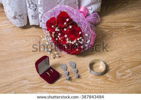 a bouquet of red roses, wedding dress, wedding rings in red box bride earrings and bracelet on a wooden background, preparation for the wedding - stock photo