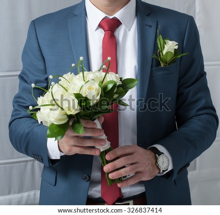 a bouquet of roses in hands of the groom