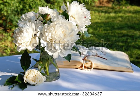 A bouquet of white peony flowers in a glass vase on a garden table in summer evening with an open book, a string of pearls and eyeglasses on blur background - stock photo