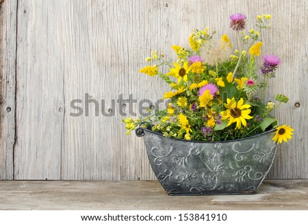 A bouquet of wildflowers in a metal container - stock photo