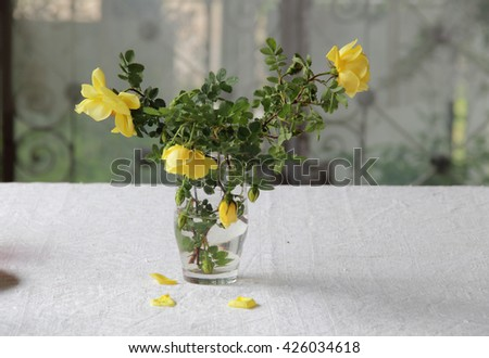 a bouquet of yellow roses in a transparent glass