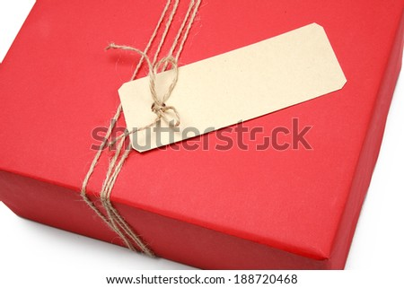 A bow from a string on a red box wrapping / studio photo of giftbox with a tag - on white background
