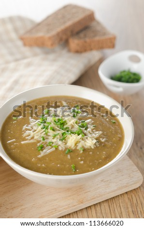 A bowl a lentil soup with cheese and green onions