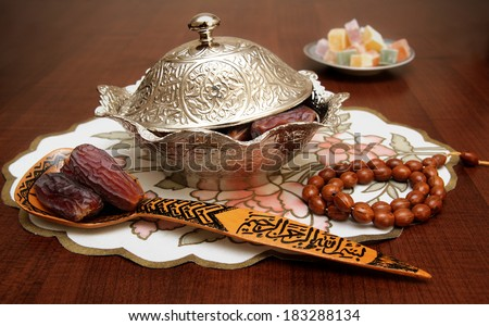 "A bowl and wooden spoon full of palm-date fruits symbolizing Ramadan with turkish delights in the background. The words ""Bismillah"" engraved on wooden spoon."