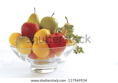 a bowl filled with pears, apples, oranges, and mangos with a branch of green leafs