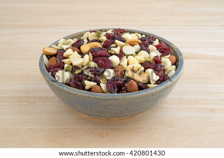 A bowl full of an assortment of nuts and dried cranberries trail mix on a wood table top. - stock photo