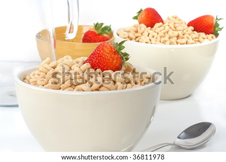 A bowl full of cereal with strawberries on the top