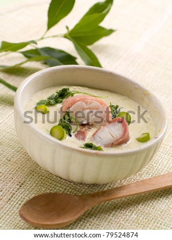 A bowl of asparagus creamy soup with fish, bacon and parsley