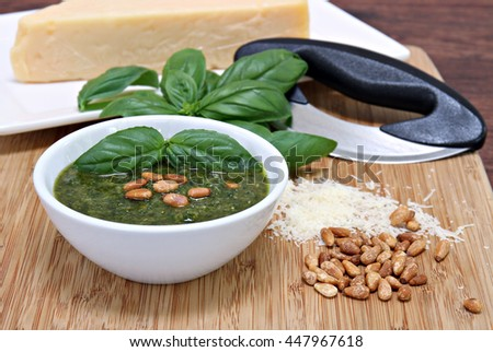 A bowl of basil pesto sauce garnished with pignoli nuts on a cutting board with parmesan and a mezzaluna knife. Selective focus on basil garnish and pignolis.