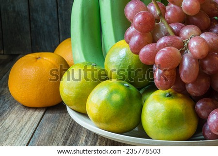 A bowl of beautiful fresh fruit, including bananas,grapes,oranges