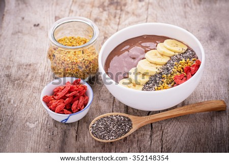 A bowl of breakfast with chocolate banana smoothies garnished with bee pollen, chia seeds, goji berries and banana on a wooden background. The concept of proper nutrition. Top view, Selective Focus - stock photo