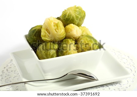 A bowl of brussels sprouts, with a serving spoon