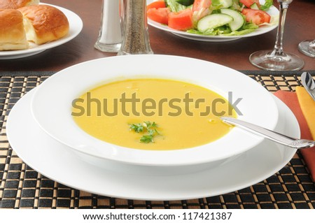 A bowl of butternut squash soup with a salad
